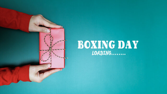 Boxing Day loading, young woman hand with a gift box offer to re
