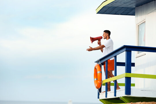 Male lifeguard with megaphone on watch tower against blue sky