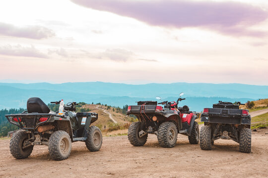 people riding on all terrain vehicle by mountains
