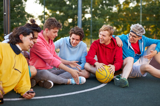 relaxed male teens have rest after sport games, basketball outdoors in court. caucasian boys in casual wear enjoy spending time with friends