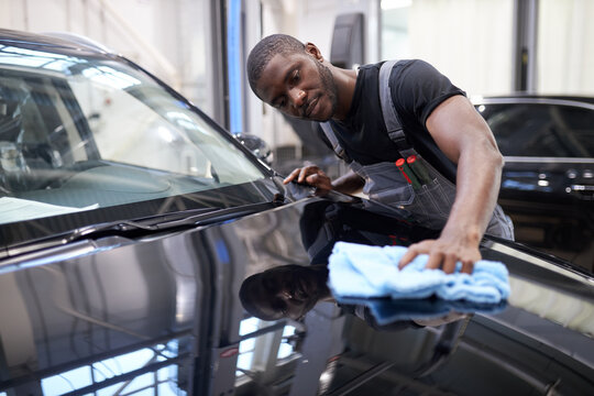 afro american auto mechanic man wipes the perfect surface of the machine after polishing, preparing a car for owner after repair