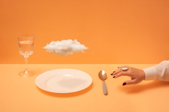 Woman's hand reaching towards cloud on plate