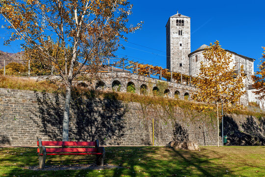Old stone church and belfry tower under blue sky in autumn in Locarno, Switzerland.