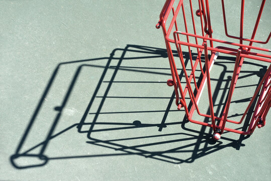 Closeup of red metal basket for automatic pick up of loose tennis balls. On a court with shadows.