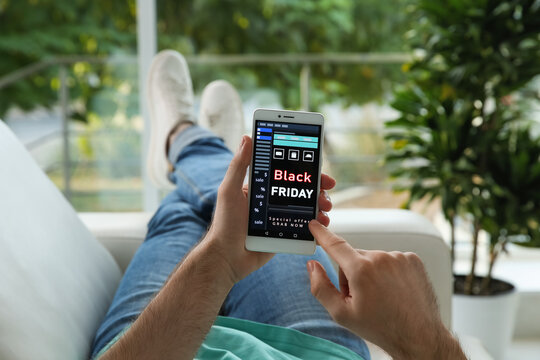 Man shopping online using smartphone on couch at home, closeup. Black Friday Sale