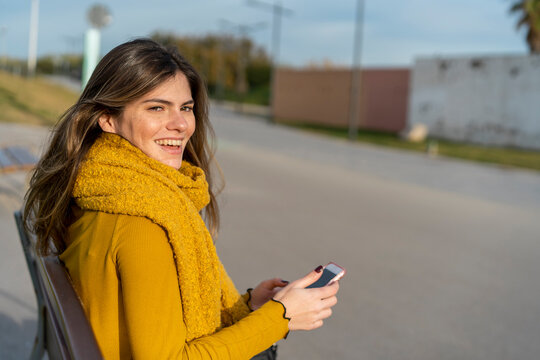 Smiling woman with mobile phone sitting on bench in park