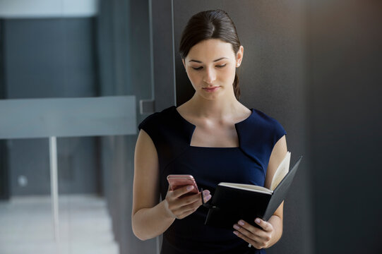 Confident businesswoman holding diary using smart phone while standing against wall