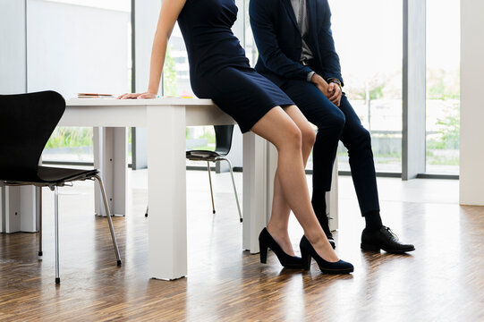 Male and female colleagues sitting on desk in office