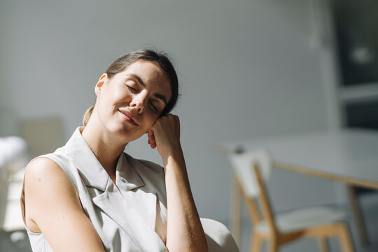 Woman with head in hands day dreaming while sitting on chair at office