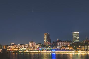 Germany, Hamburg, St. Pauli buildings illuminated at night seen across Elbe river Fotomurales