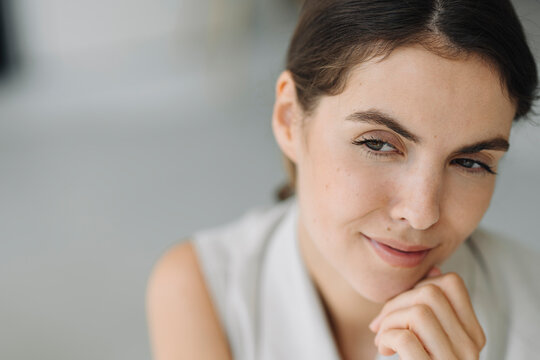 Young woman with hand on chin day dreaming at office