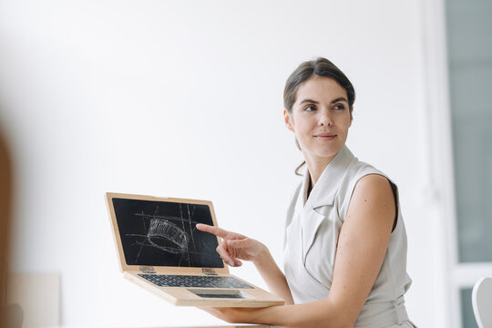 Smiling businesswoman showing infographic on laptop at office