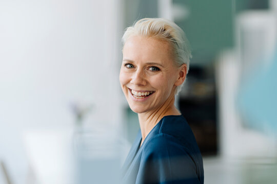 Close-up of cheerful businesswoman with short hair in office