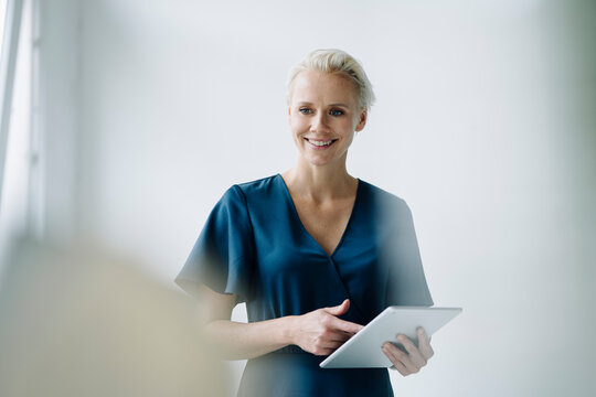 Female professional using digital tablet looking away while standing against wall in office