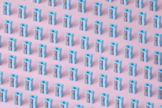 Pattern of blue erasers against pink background