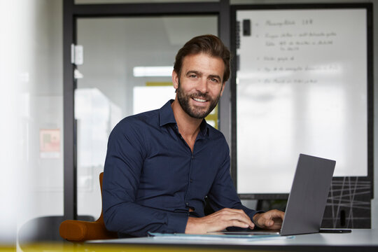 Smiling man working on laptop while sitting by desk in office