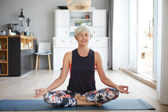 Active senior woman meditating on exercise mat at home