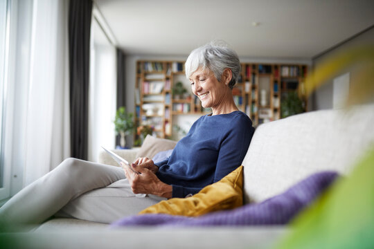 Smiling woman looking in digital tablet while sitting at home on sofa