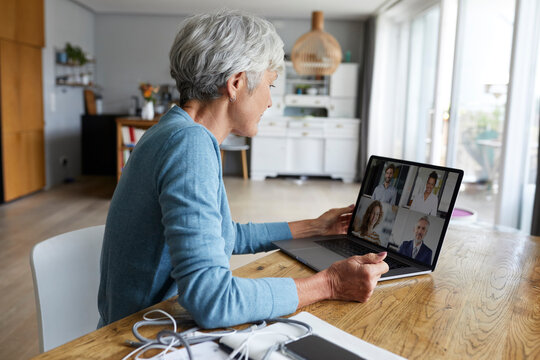 Active senior woman attending meeting on video conference while sitting at home