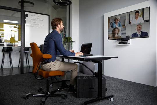 Businessman attending web conference while sitting in office