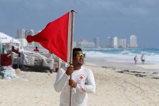 A lifeguard places a red flag on the beach to warn beachgoers of hazards due to the proximity of Hurricane Zeta in Cancun