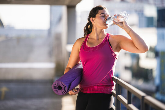 Young woman holding exercise mat drinking water while standing by railing on terrace