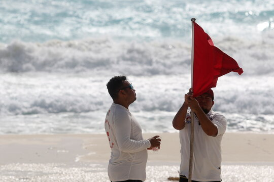 Lifeguards place a red flag on the beach to warn beachgoers of hazards due to the proximity of Hurricane Zeta in Cancun
