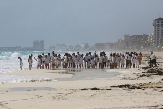 Members of a religious group gather at the beach as Hurricane Zeta approaches Cancun