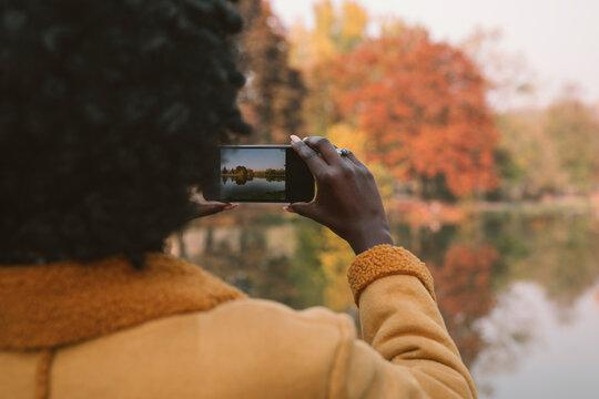 Woman taking photo of the autumn scenery
