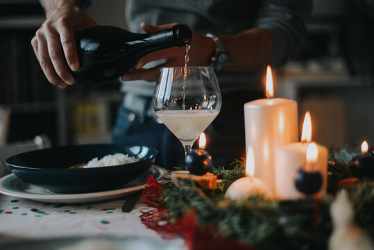 A man pours a champagne on a Christmas party
