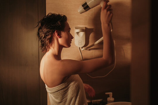 Young female drying wet hair in bathroom