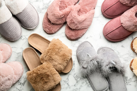 Many different soft slippers on white marble background, flat lay