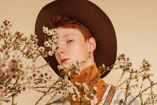 Extravagant male model in hat standing in studio with flowers