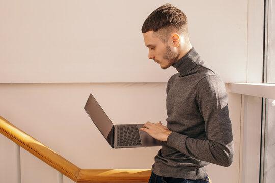 Young man using laptop near window