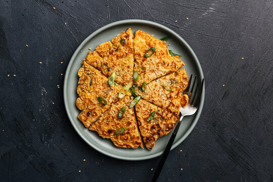 kimchi pancake on plate with green onions