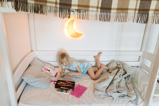 Little girl drawing picture on her bed