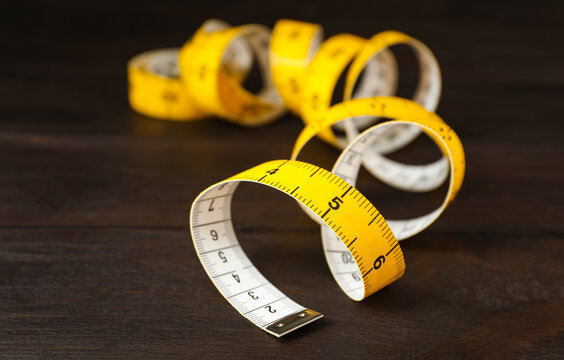 Yellow measuring tape on brown wooden table, closeup