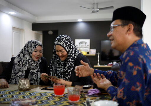 Tengku Shawal talks as his daughter and sister reminisce over old family photos in Singapore
