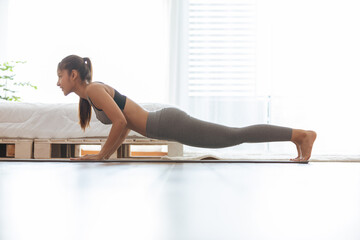 Attractive Asian woman practice yoga Plank pose to meditation in bedroom after wake up in the morning Feeling so comfortable and relax,Healthcare Concept