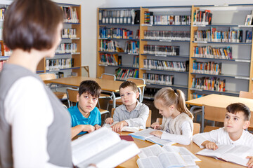 Group of school kids studying in school library with friendly female teacher..