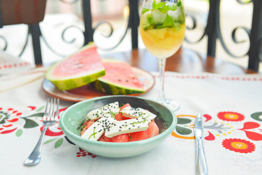 Greek watermelon salad with feta cheese and basil. Delicious summer meal in a restaurant outside, eating out concept.