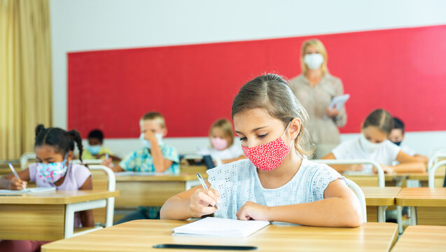 Diligent tween girl in protective mask studying in school with classmates. New life reality in coronavirus pandemic