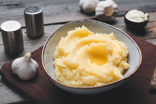 Bowl with tasty mashed potato and garlic on table