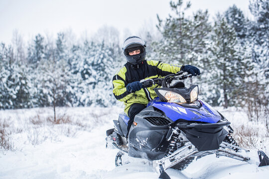 Man driving snowmobile in snowy forest. Man on snowmobile in winter mountain. Snowmobile driving