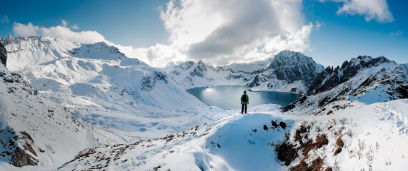 Hiking on snowshoes on a trail. Man trekking in snow covered mountain landscape overlooking Luenersee lake. Sunny day and a hikers on a top of a peak
