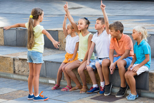 Cheerful boys and girls in school age having fun playing charades