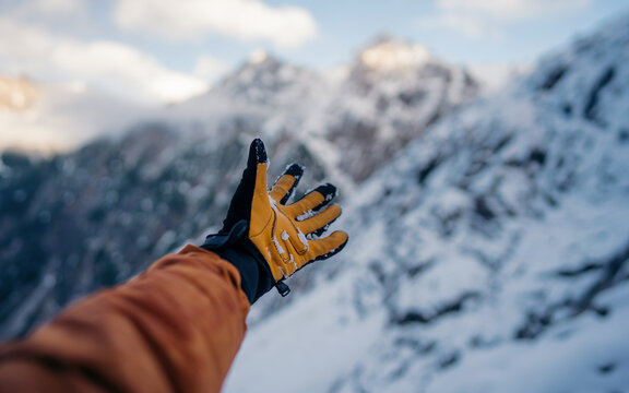 Hand winter sport glove on snow, ice and rock in the background. Snow and ice, blue sky. Winter climbing, hiking and ski touring. Point of view of an climbing tool in a hand of an alpinist.