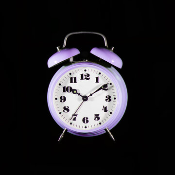 Classic purple table alarm clock on a black background