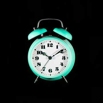 Classic table alarm clock green color on a black background