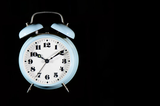 Classic table alarm clock in light blue color on a black background